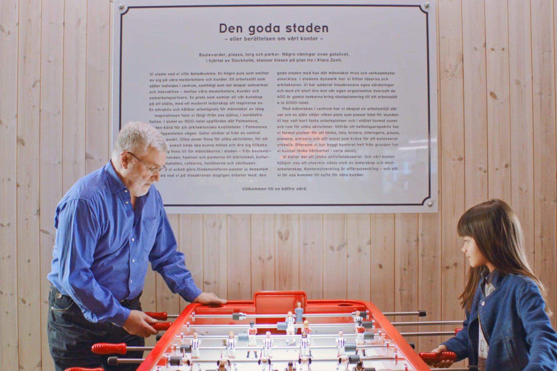 Bild som visar en pensionär och en liten flicka som spelar fussball på Vasakronans huvudkontor
