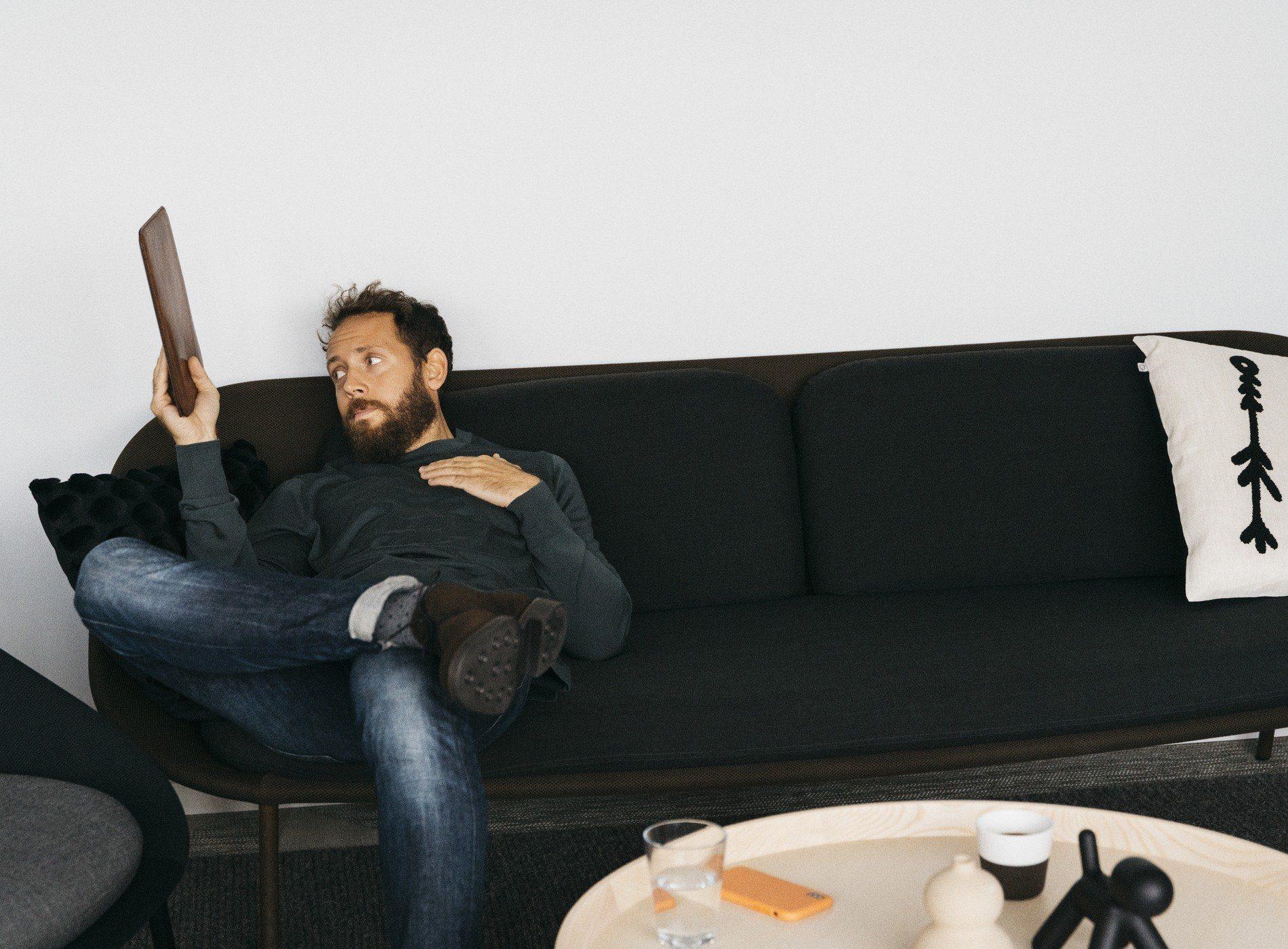 Man sitter i en soffa med en iPad.