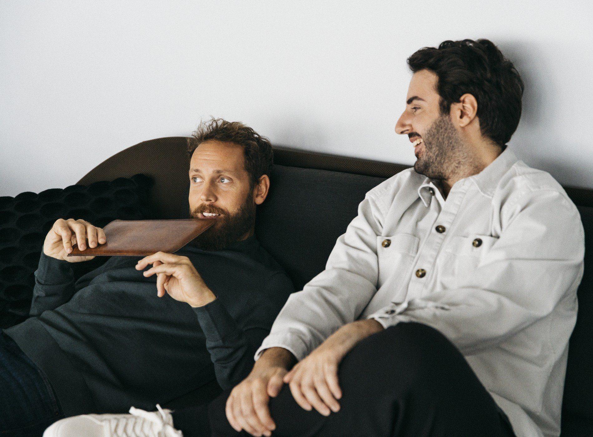 Två kollegor sitter i en soffa med en iPad.